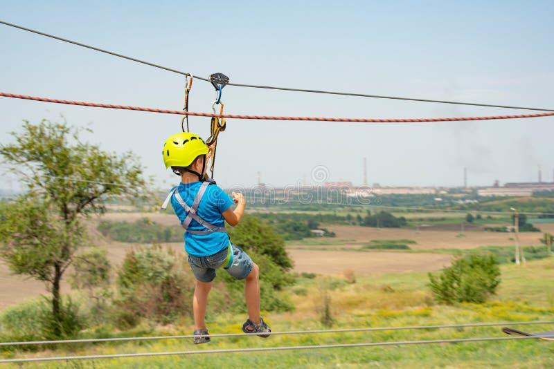 Un muchacho vestido en un casco y un seguro protectores, va abajo de la cuerda, desciende sosteniendo un cable protector fotos de archivo
