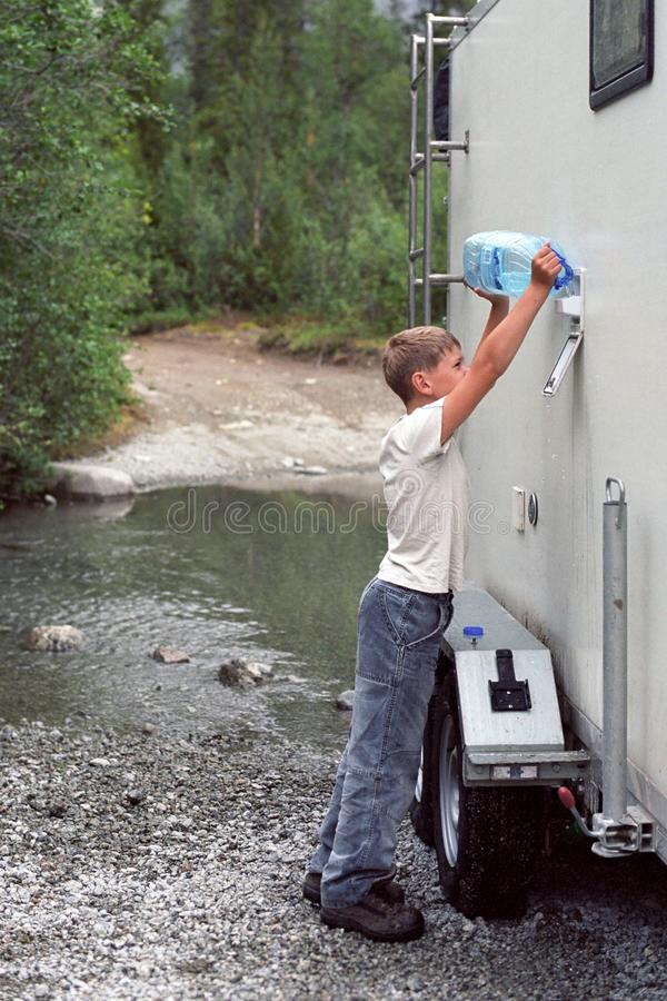 Un muchacho vierte el agua en un campista de un río del bosque de una botella del cinco-litro fotos de archivo