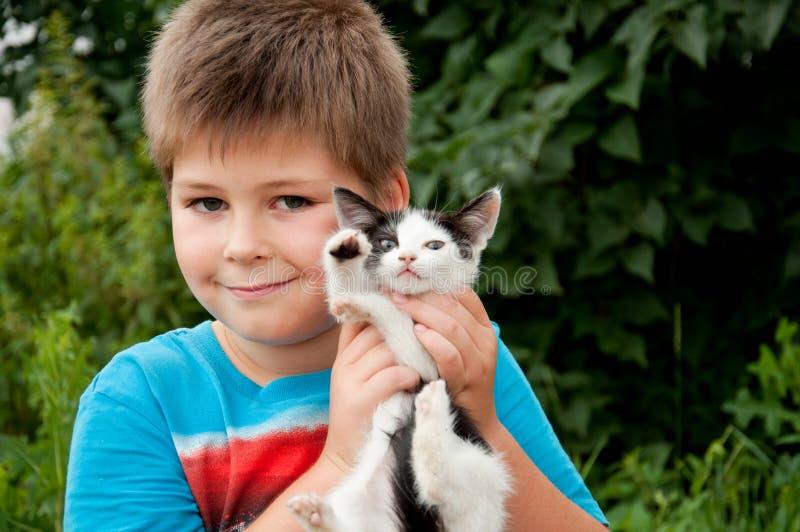 Un muchacho y un gatito divertido foto de archivo libre de regalías