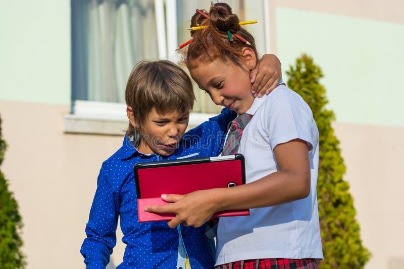 Un muchacho y una muchacha están jugando en las tabletas imagen de archivo libre de regalías