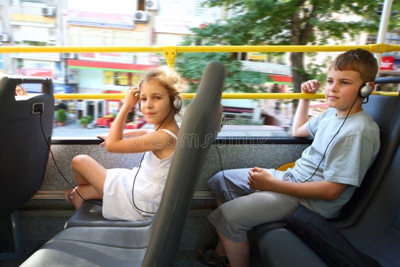 Un muchacho y una muchacha que viajan en un bus turístico foto de archivo libre de regalías