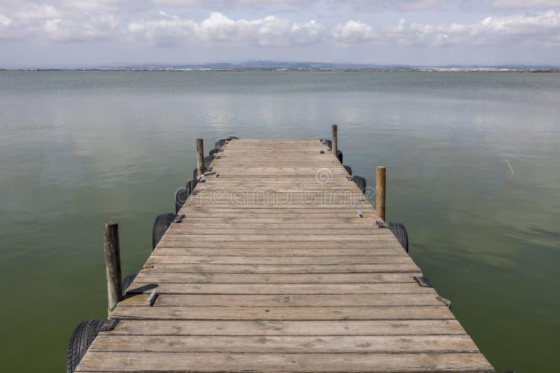 Un muelle por el lago en el cielo de la mañana foto de archivo