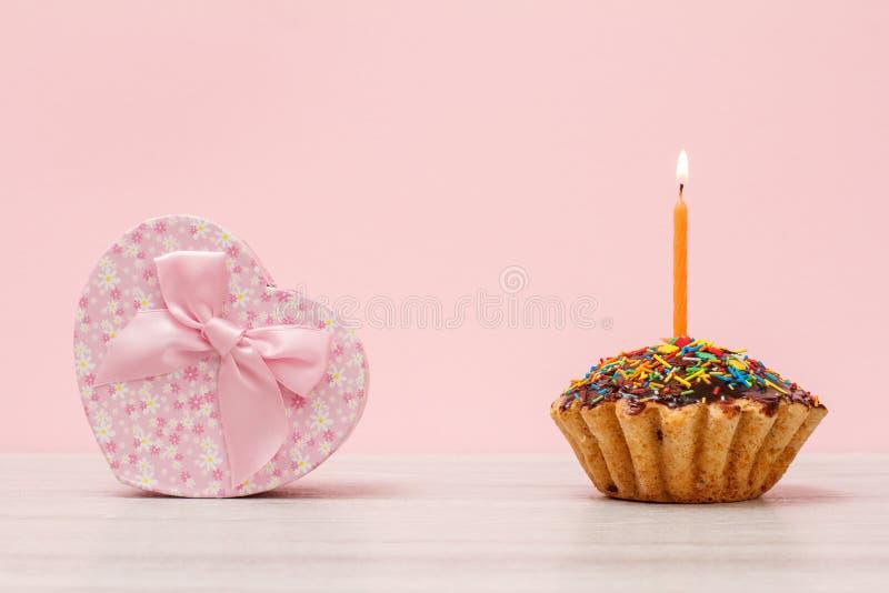 Un muffin d'anniversaire avec une bougie festive en feu et une boîte cadeau sur fond rose photographie stock libre de droits
