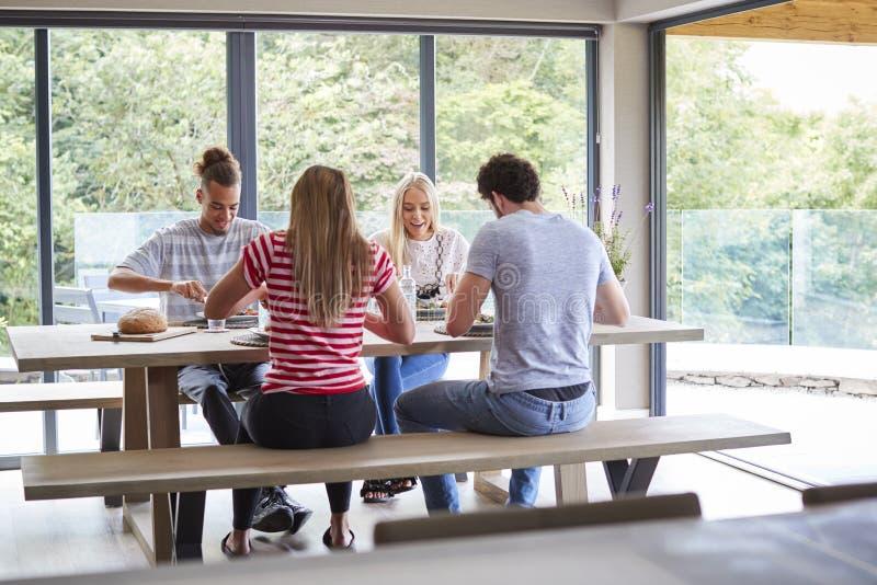 Un multi gruppo etnico di quattro giovani amici adulti che mangiano ad un partito di cena casuale in una sala da pranzo moderna fotografia stock