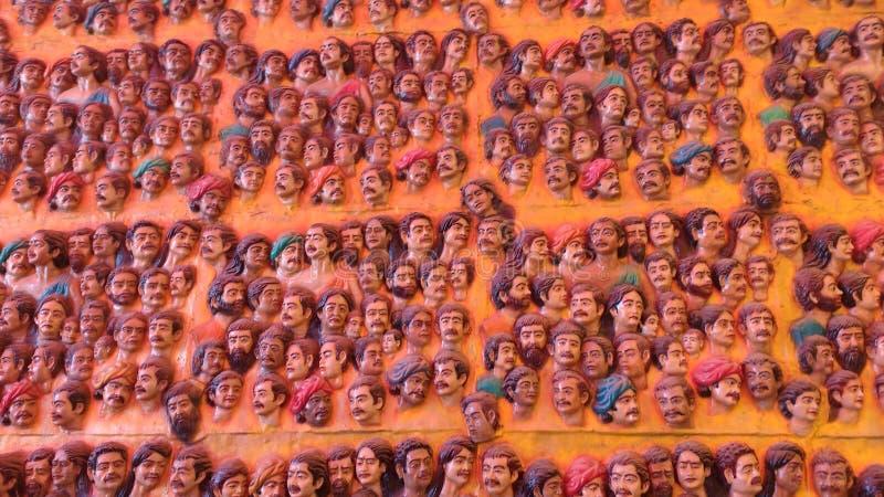 Un mur avec des visages des statues photographie stock