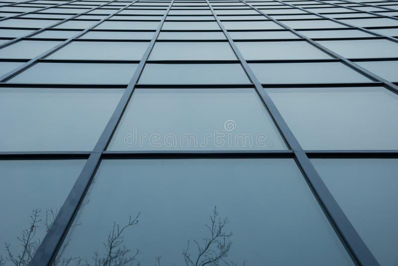 Un mur d'un bâtiment des fenêtres carrées en verre bleues image stock