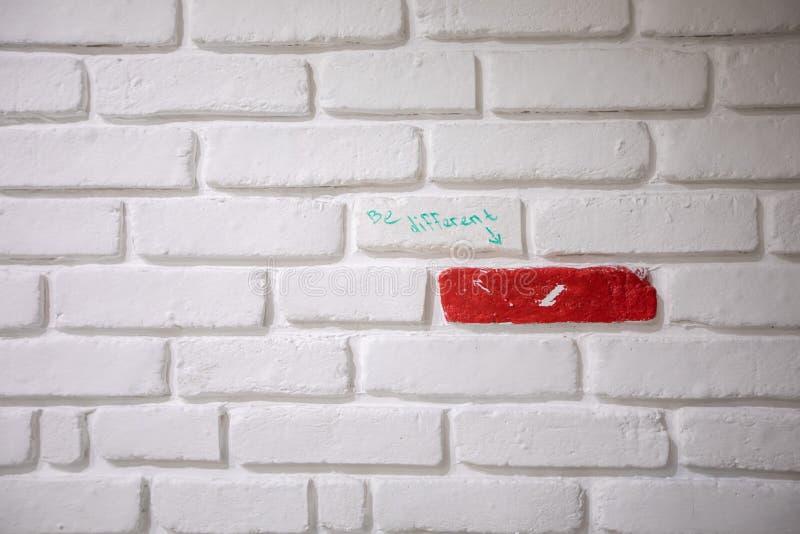 Un mur de briques blanc avec une brique rouge et ?criture image libre de droits