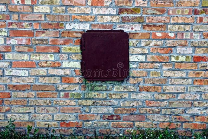 Un mur de briques dans l'herbe avec un couvercle fermé de fer image stock