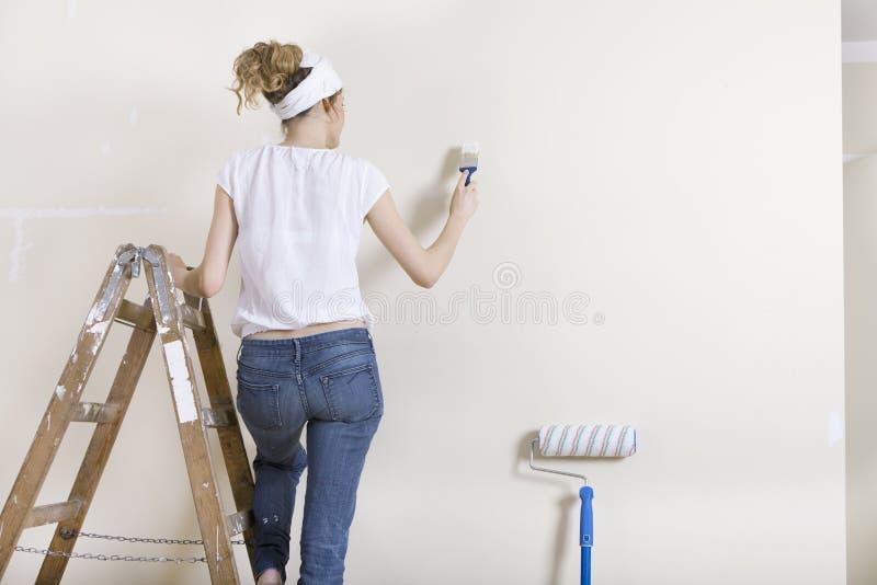 Un mur de peinture de femme sur l'échelle image stock