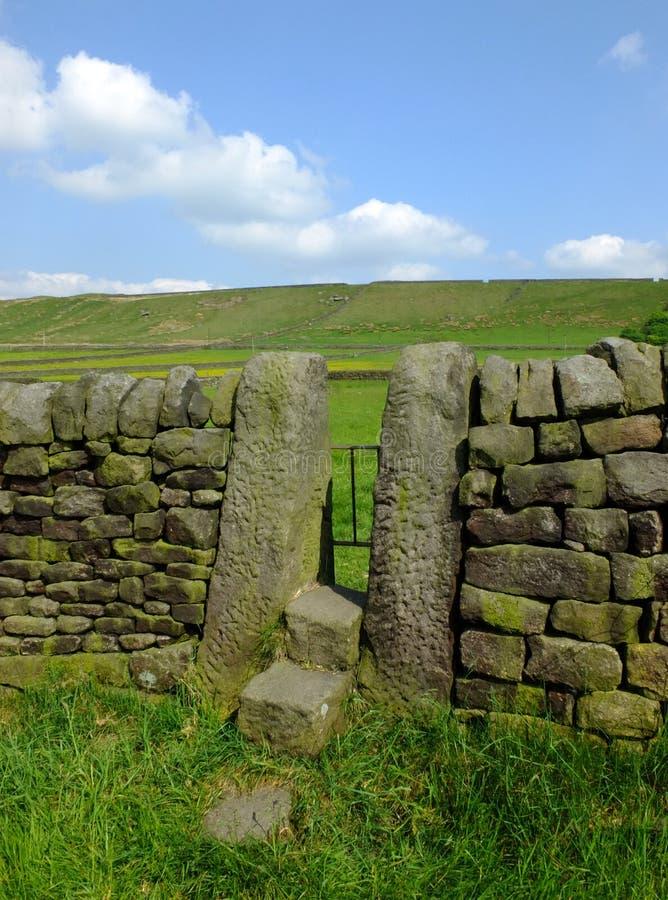 Un mur de pierres sèches avec le montant en pierre ou la porte étroite avec des étapes dans un pré de flanc de coteau de vallées  image libre de droits