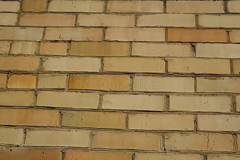 Un mur fait en brique jaune, capable de la portion comme fond photos stock