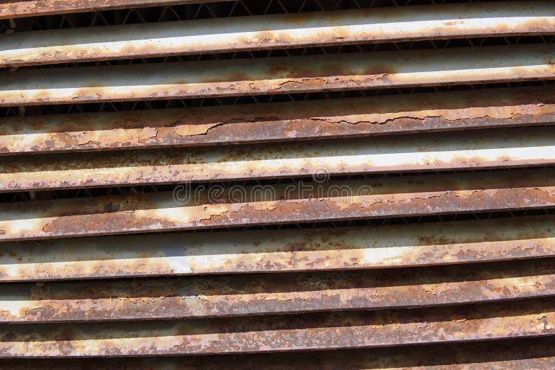 Un muro di mattoni con una griglia arrugginita del ferro fotografie stock