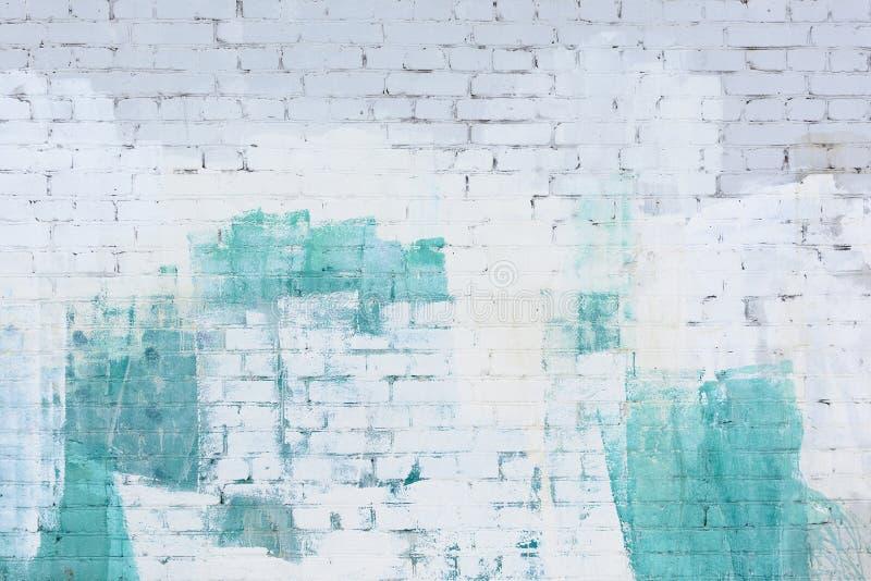 Un muro di mattoni ha dipinto l'estratto con bianco e la pittura del turchese Fondo, struttura immagini stock