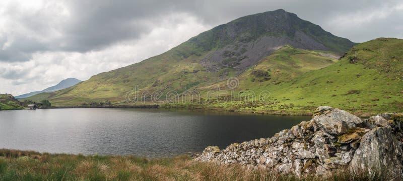 Un muro a secco conduce al lago di pesca di Llyn Dywarchen nel parco nazionale di Snowdonia immagini stock
