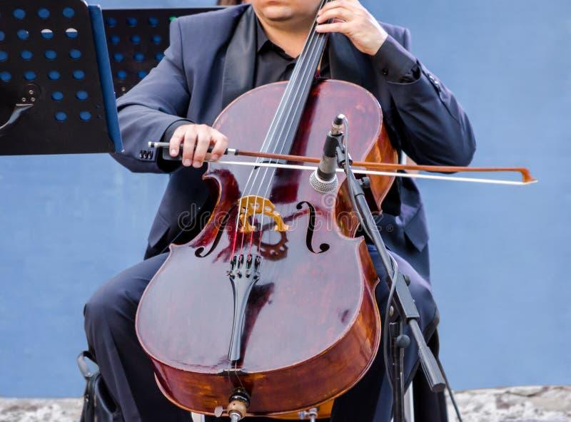 un musicien dans le costume bleu jouant le violoncelle images stock