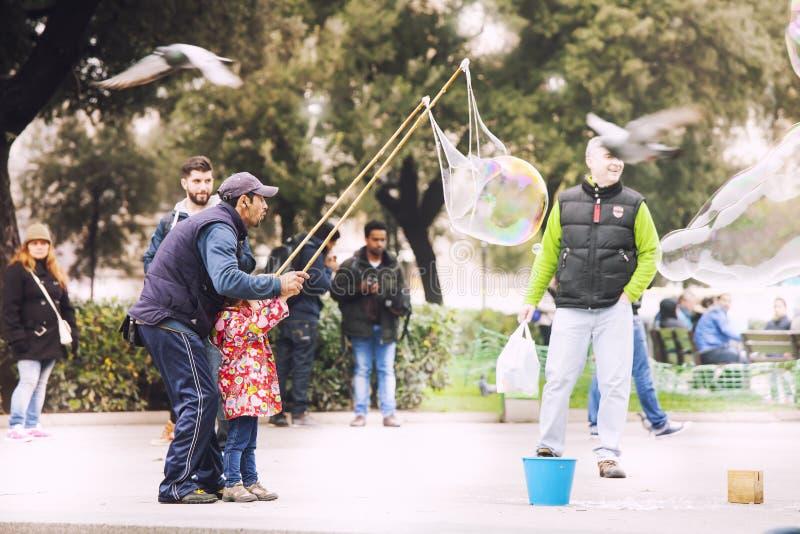 Un musicien de rue d'homme avec une petite fille fait les grandes bulles de savon photo libre de droits