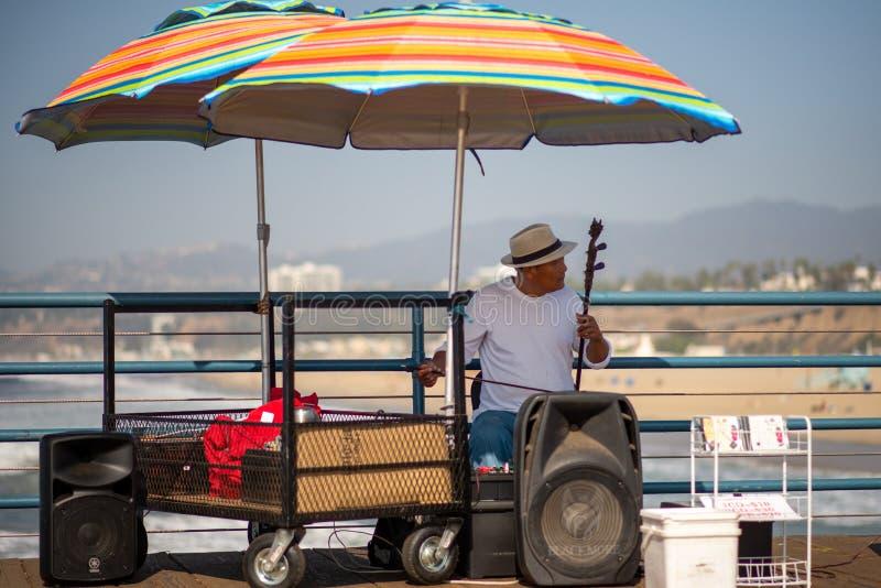 Un musicien de rue joue un instrument de musique sur Santa Monica Pier pour les touristes qui visitent Los Angeles, la Californie photos stock
