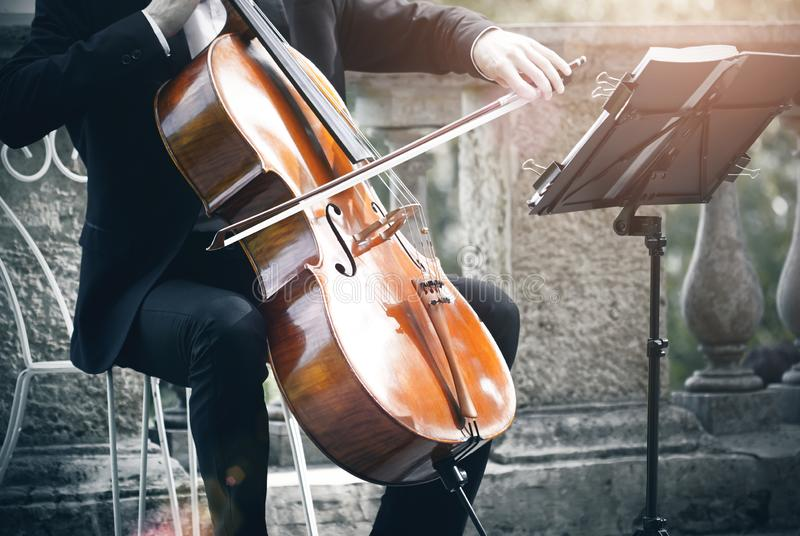 Un musicien joue le violoncelle avec un arc et regarder la notation musicale images stock
