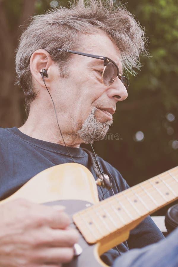 Un musicien masculin plus âgé jouant la guitare sur une rue de New York City image stock
