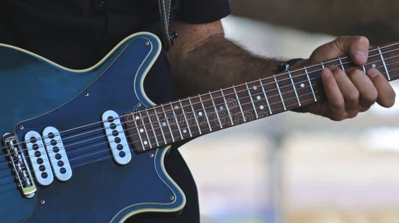 Un musicien Plays une guitare électrique bleue photos libres de droits