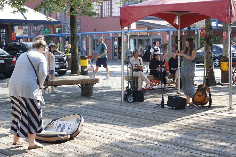 Un musicista ambulante esegue alle punte dell'isola di Granville e di un turista mentre esegue L'isola di Granville a Vancouver h fotografia stock libera da diritti