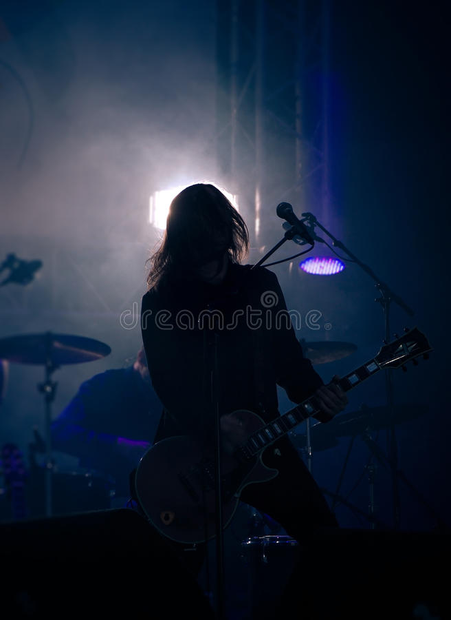 Un musicista con una chitarra su un concerto fotografie stock