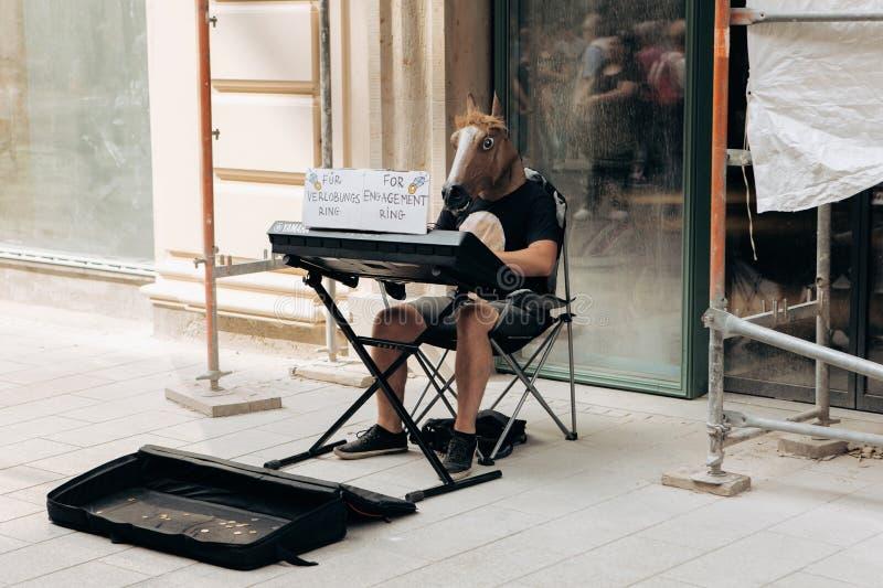 Un musicista creativo con una testa del cavallo gioca su un sintetizzatore sulla via di Lipsia fotografia stock