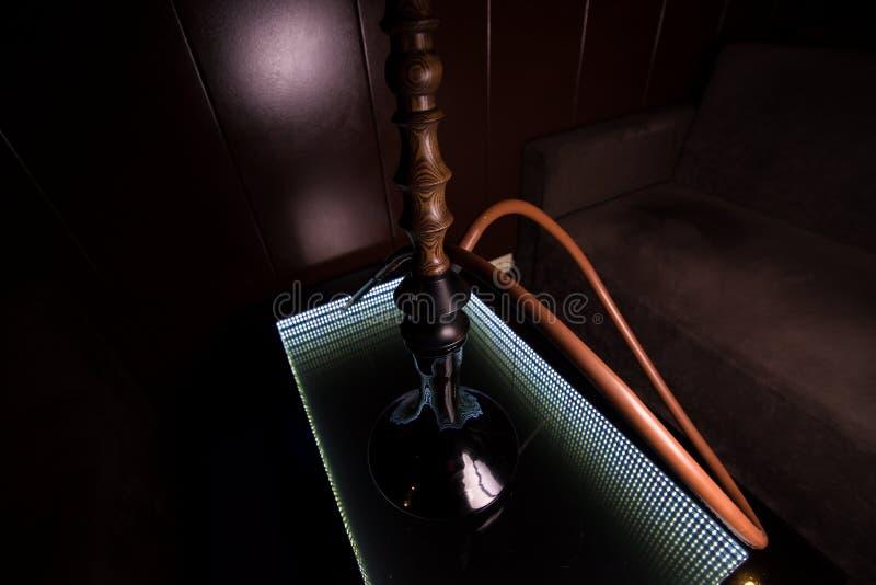 Un narguilé noir se tient sur une table en verre photographie stock
