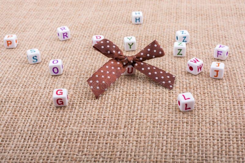 Un nastro ed i cubi dado di taglia sparsi di alfabeto su una superficie strutturata fotografie stock