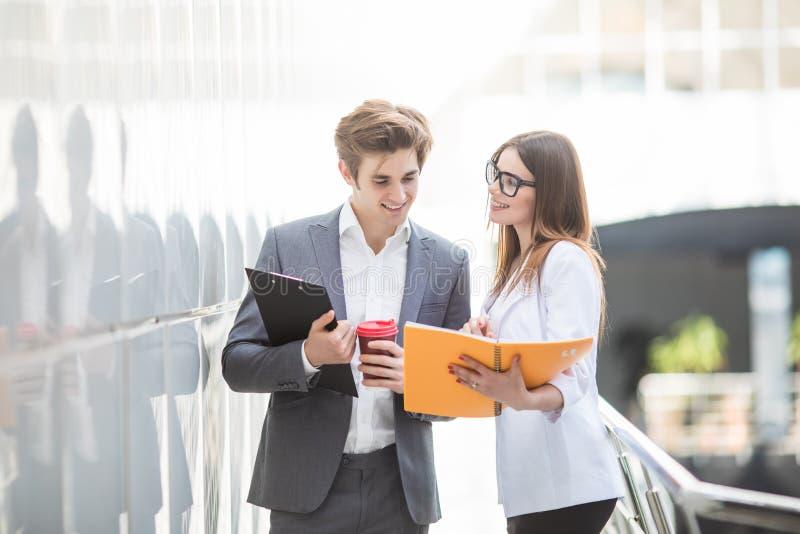 Un negocio diverso del hombre y de la mujer combina en su edificio de oficinas de la compañía que camina en pasillo y disscuss so imagenes de archivo