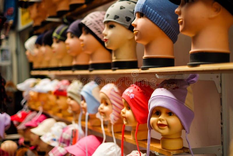 Un negozio con i cappucci dei bambini e del bambino sulle teste della bambola fotografia stock