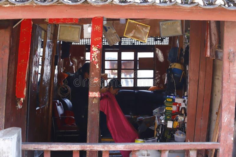 Un negozio di barbiere del parrucchiere lungo la via nel villaggio di Shigu, il Yunnan, Cina immagine stock