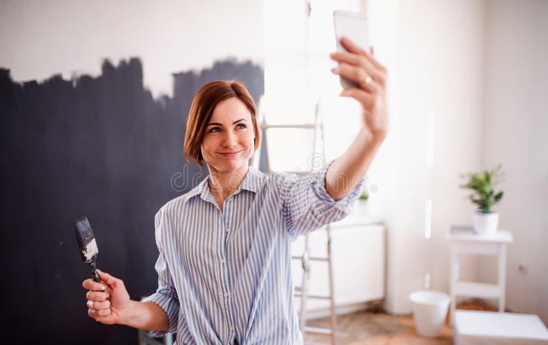 Un negro de la pared de la pintura de la mujer joven, tomando el selfie Un inicio de la peque?a empresa imagenes de archivo