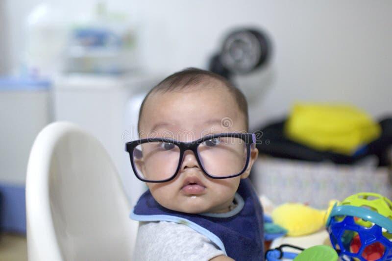 Un neonato sta indossando un paio dei vetri dell'occhio immagini stock
