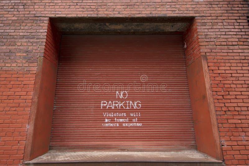 Un nessun parcheggio dipinto su una porta del magazzino fotografia stock