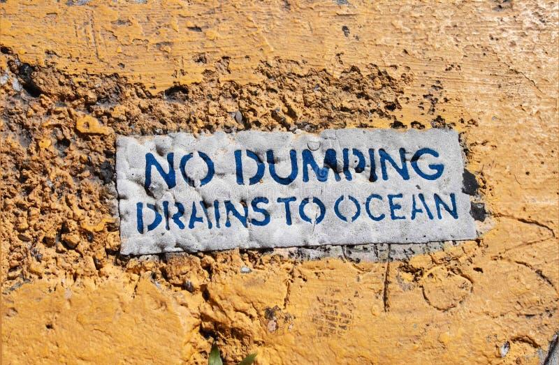 Un nessuno dumping - gli scoli all'oceano firmano sul marciapiede dipinto giallo grungy approssimativo fotografie stock libere da diritti
