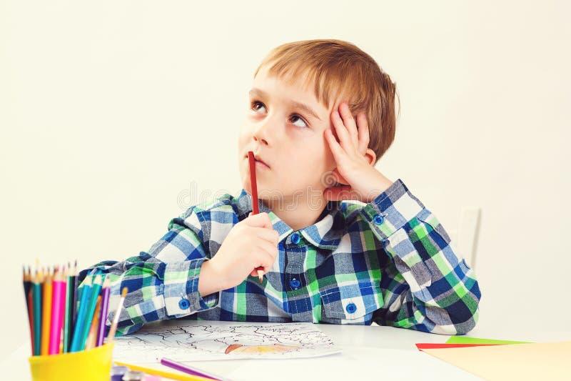 Un niñito corto dibuja con lápices en clase de arte Feliz hijo tiene una nueva idea Concepto de educación, desarrollo y creativid foto de archivo