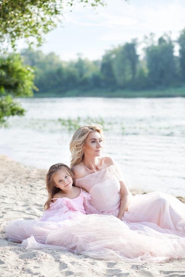 Un niño alegre y su madre están disfrutando de la mañana soleada cerca del agua Retrato de una madre rubia hermosa y de su daugh imágenes de archivo libres de regalías