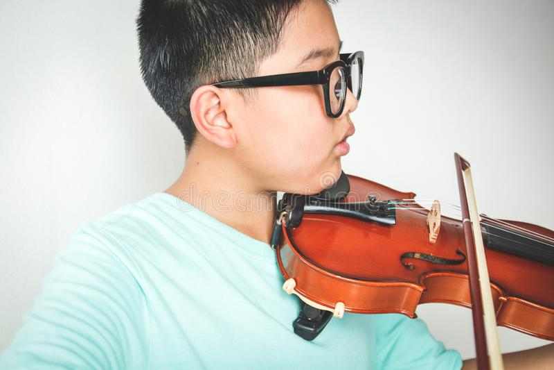 Un niño asiático está tocando el violín foto de archivo