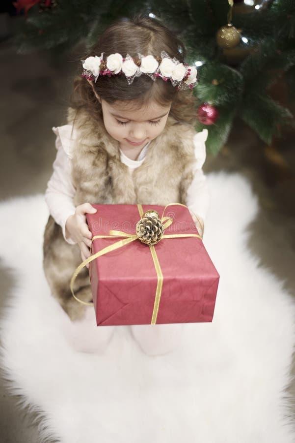 Un niño bonito de la niña sostiene un regalo grande de la Navidad delante de un árbol de navidad Concepto de la Navidad, fondo imagen de archivo libre de regalías