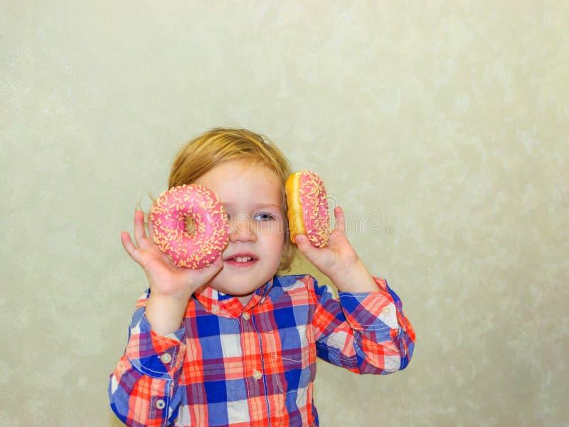 Un niño celebra los anillos de espuma cerca de sus ojos y las miradas a través de los agujeros como los vidrios directos imagen de archivo
