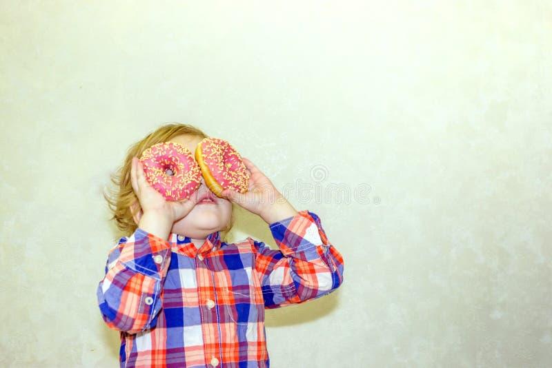 Un niño celebra los anillos de espuma cerca de sus ojos y las miradas a través de los agujeros como los vidrios directos fotos de archivo libres de regalías