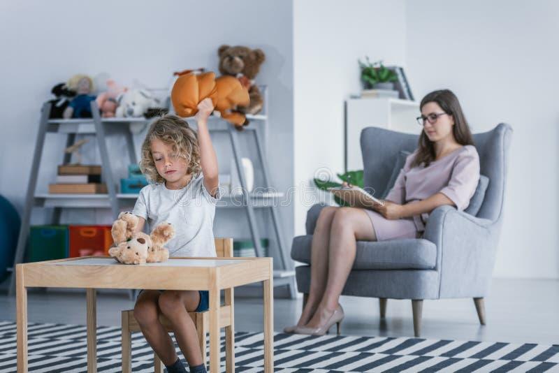 Un niño con los problemas del comportamiento que golpean un oso de peluche durante una reunión terapéutica con un terapeuta en a foto de archivo libre de regalías