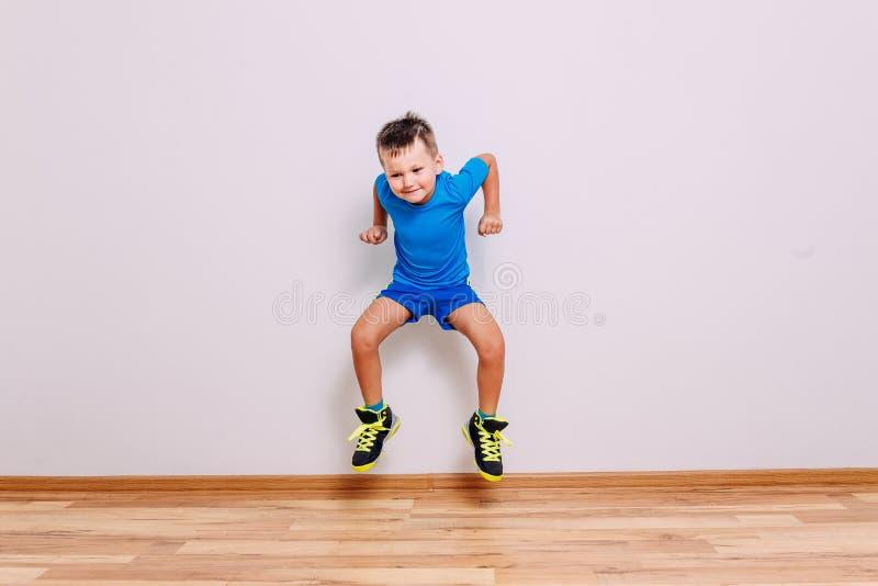 Un niño de cinco años en zapatillas de deporte limpias del baloncesto y saltos uniformes de los deportes altos en un fondo blanco foto de archivo libre de regalías