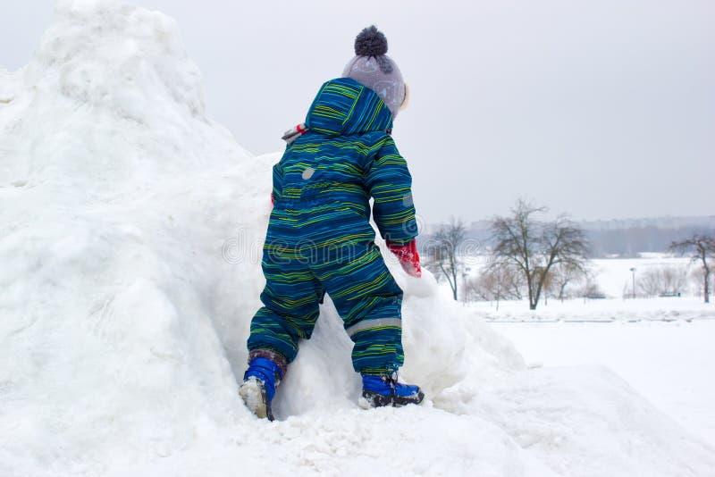 Un niño de cuatro años, muchacho, está subiendo una colina nevosa imagenes de archivo