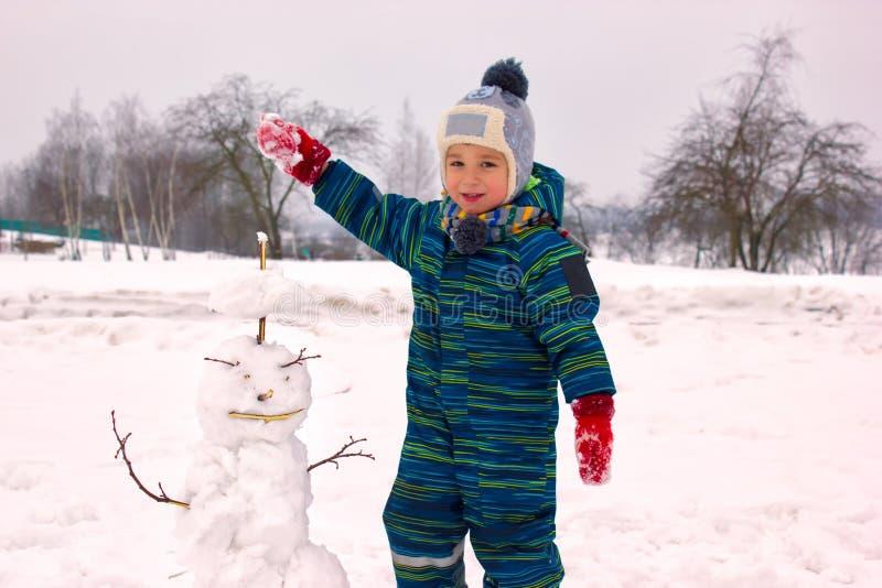 Un niño de cuatro años, muchacho, sonriendo esculpe un muñeco de nieve fotos de archivo