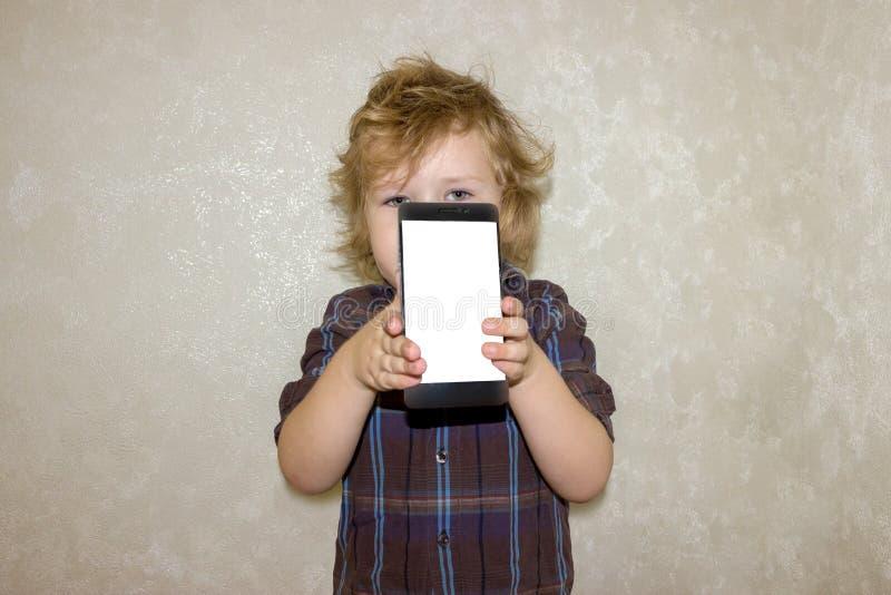 Un niño del muchacho mira en la cámara de un smartphone, muestra la pantalla con su foto digital imagen de archivo libre de regalías