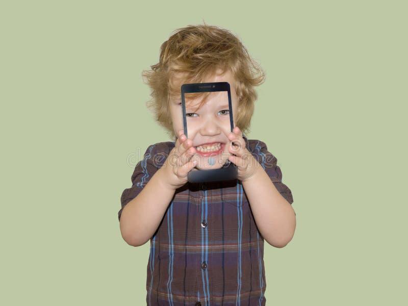 Un niño del muchacho mira en la cámara de un smartphone, muestra la pantalla con su foto digital imágenes de archivo libres de regalías