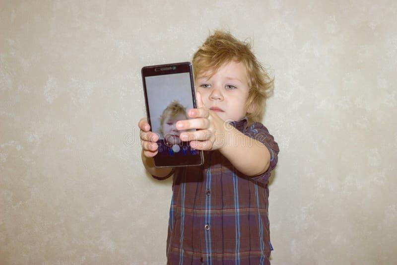 Un niño del muchacho mira en la cámara de un smartphone, muestra la pantalla con su foto digital foto de archivo libre de regalías