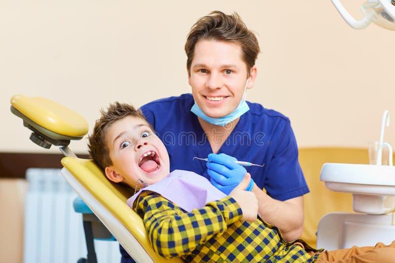 Un niño del muchacho y un hombre del dentista aumentaron sus pulgares fotos de archivo libres de regalías